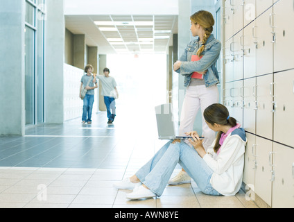 Two high school girls by lockers, watching teen boys approaching - Stock Photo