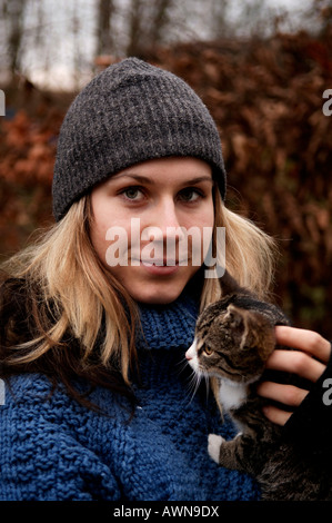 Portrait of a blonde young woman wearing wool hat, holding a small cat on her arm - Stock Photo