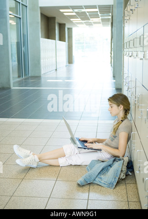High school girl using laptop in school hallway - Stock Photo