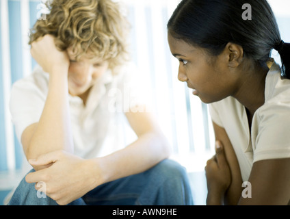 Teen boy and girl having serious conversation - Stock Photo