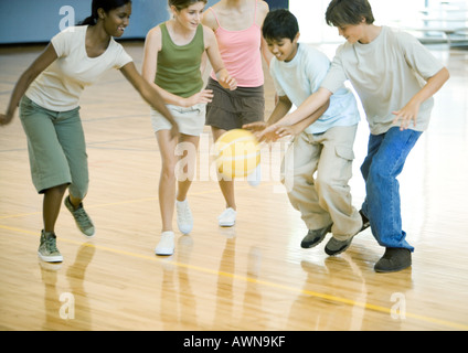 High school students playing basketball in school gym - Stock Photo