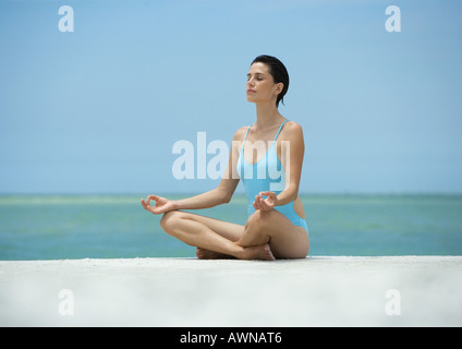 Woman sitting in lotus position, on beach - Stock Photo