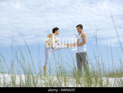 Man helping woman stretch leg on beach - Stock Photo