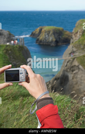 Woman photographing carrick-a-rede bridge - Stock Photo