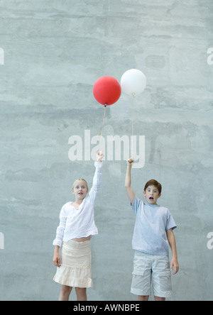 Two children holding balloons, making faces - Stock Photo