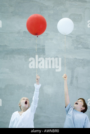 Two children holding balloons and making faces - Stock Photo