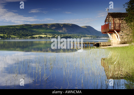 Dawn on Ullswater, near Pooley Bridge. Still water with reflections and reeds on a bright blue summer morning in - Stock Photo