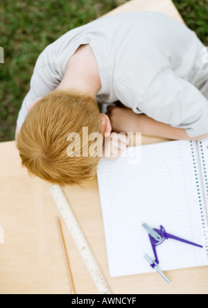 Boy with head on table next to open notebook - Stock Photo