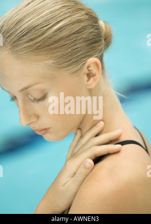Woman with hand on shoulder, pool in background - Stock Photo