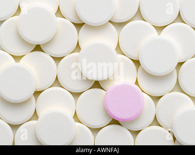 A pink tablet amongst white tablets - Stock Photo