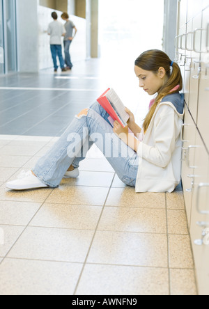 Girl sitting on floor in school hallway, leaning against lockers and studying - Stock Photo