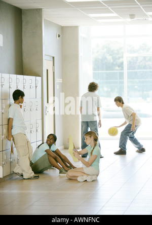 Kids hanging out in hallway of secondary school - Stock Photo