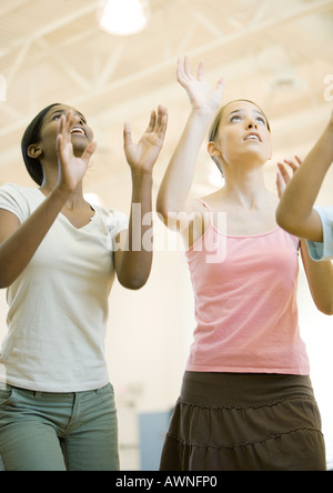 Teenage girls holding arms up to hit ball - Stock Photo