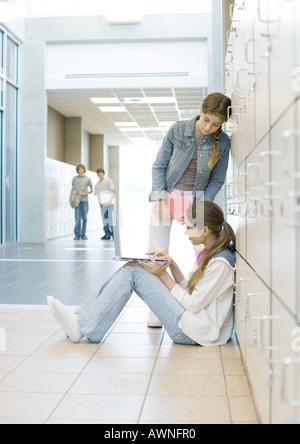 Teen girls using laptop in hallway - Stock Photo