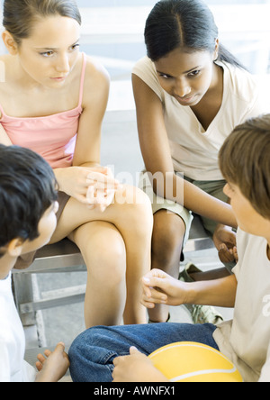 Group of high school students sitting, talking - Stock Photo