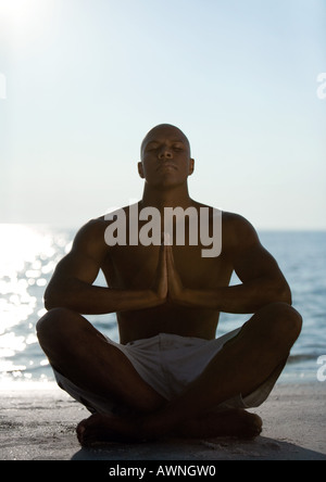 Man sitting in yoga pose on beach, silhouette - Stock Photo