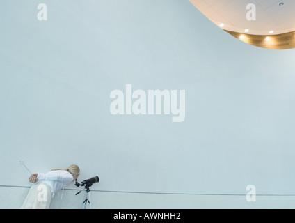 Girl looking through telescope, holding magic wand behind back