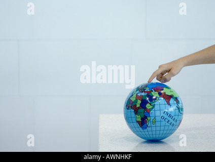 Child's hand pointing to spot on globe - Stock Photo