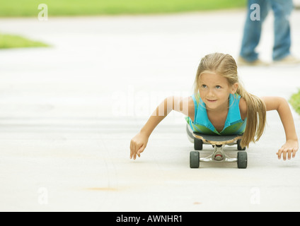 Girl lying on skateboard - Stock Photo