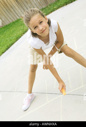 Girls drawing hopscotch squares on concrete - Stock Photo