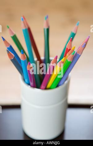 Coloured pencils in a desk tidy - Stock Photo