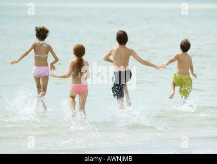 Children running in surf at beach - Stock Photo