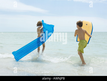 Children running in surf at beach, with raft and body board - Stock Photo
