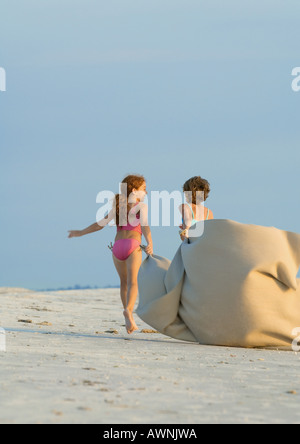 Two girls carrying blanket in wind on beach - Stock Photo