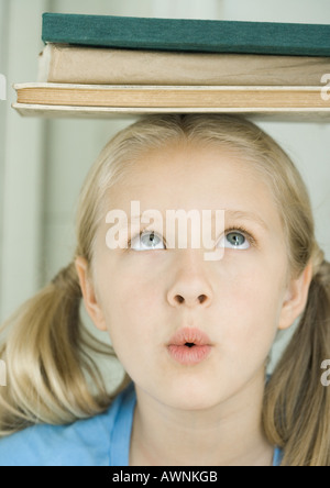 Girl with stack of books on head, making face - Stock Photo