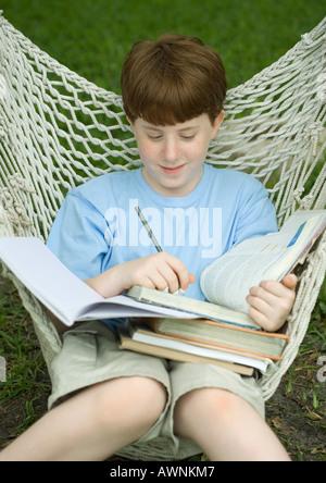 Boy sitting in hammock doing homework - Stock Photo