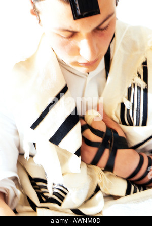 Jewish man wearing Tefillin and Tallith for prayer, close-up - Stock Photo