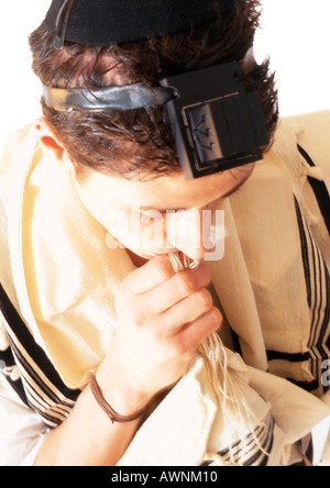 Jewish man wearing Tefillin and Tallith for prayer, high angle view, close-up - Stock Photo