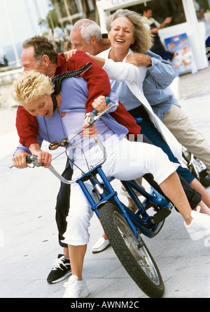 Mature men and women on tandem bike, falling to side, portrait - Stock Photo