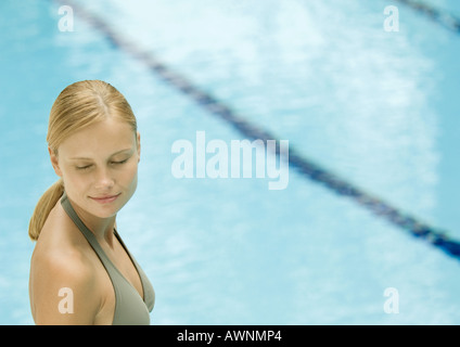 Woman near pool with eyes closed, smiling - Stock Photo