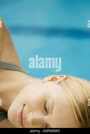 Woman reclining by pool, close-up of face - Stock Photo