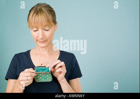 Woman looking in purse - Stock Photo