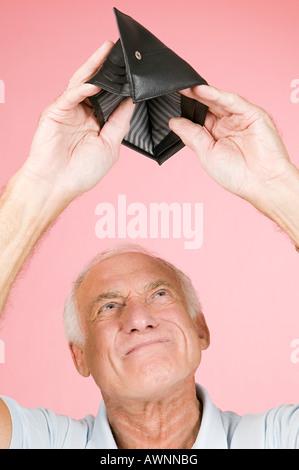 Man looking in empty wallet - Stock Photo