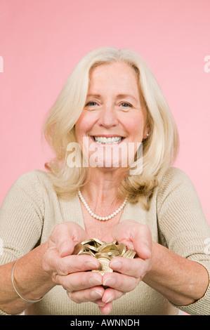 Woman holding pound coins - Stock Photo