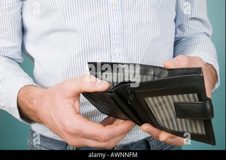 Man holding empty wallet - Stock Photo