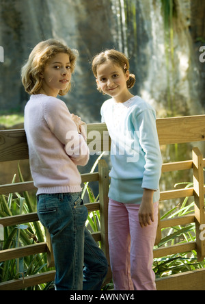 Two girls leaning against wooden fence - Stock Photo