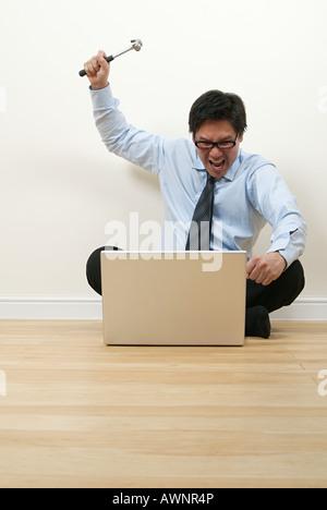 A businessman holding a hammer - Stock Photo