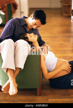 Man sitting backwards on chair and pregnant woman sitting for Sitting on the floor during pregnancy