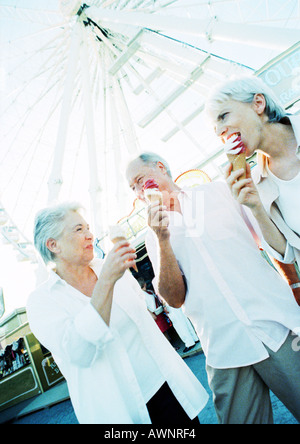 Retired friends eating ice cream in amusement park - Stock Photo