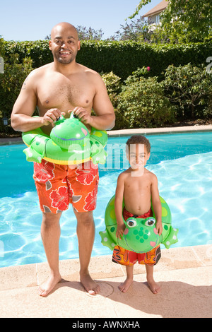 Father and son wearing identical flotation devices by pool - Stock Photo