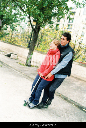 Two young people standing on push scooter - Stock Photo
