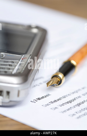 Mobile phone laying on a rental contract - Stock Photo