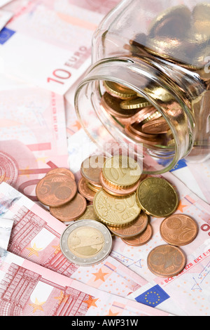 Glass jar full of coins being spilled out onto a desk covered in cash (Euros) - Stock Photo