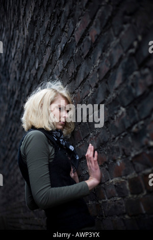 Blonde woman standing in front of a stone wall