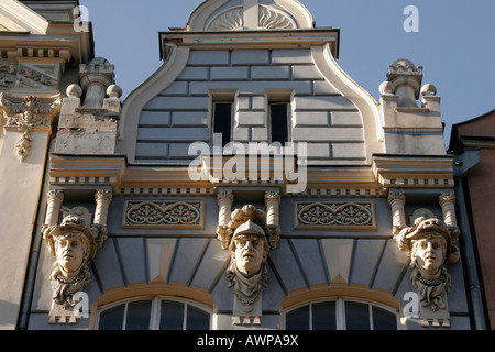 Facade featuring heads in the historic city centre of Gdansk, Poland, Europe - Stock Photo