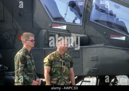 2 US military men near helicopter ready to go  - Stock Photo